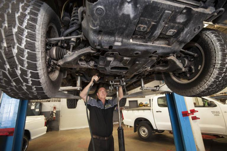 professional car mechanic working under car that is on a lift in auto adrian's balcatta car care centre