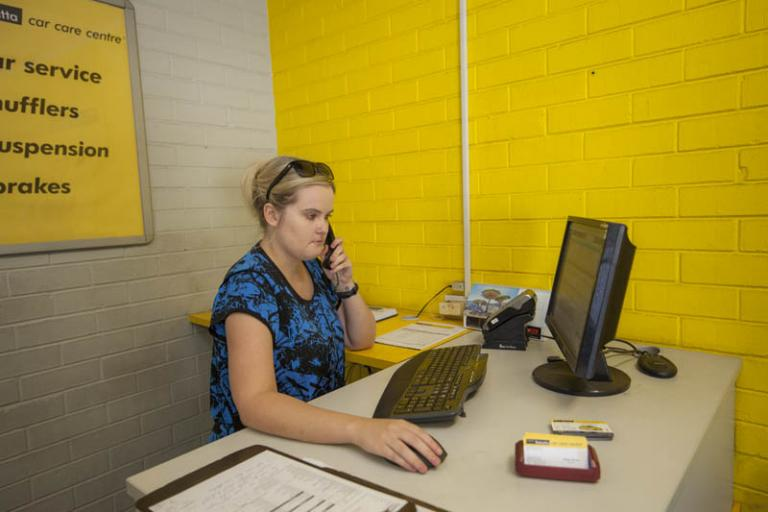 female receptionist answering phone in the reception area at adrian's balcatta car care centre