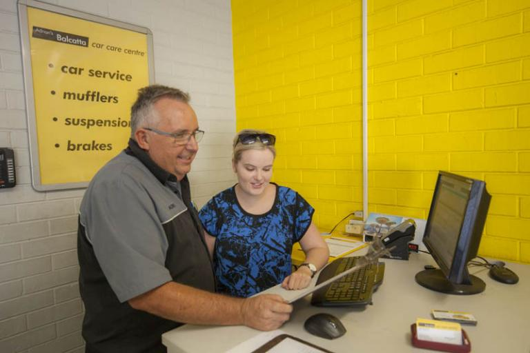 male and female employees going over the bookings for the day in the reception area at adrian's balcatta car care centre