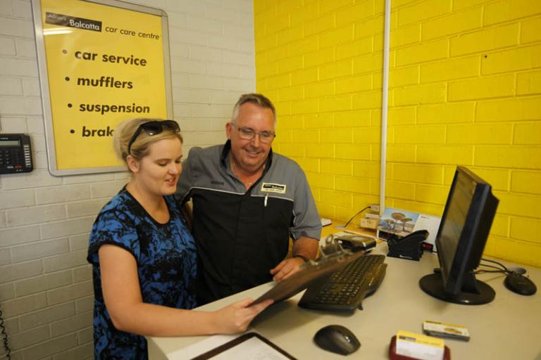 man and women going over the bookings for the day in the reception area at adrian's balcatta car care centre
