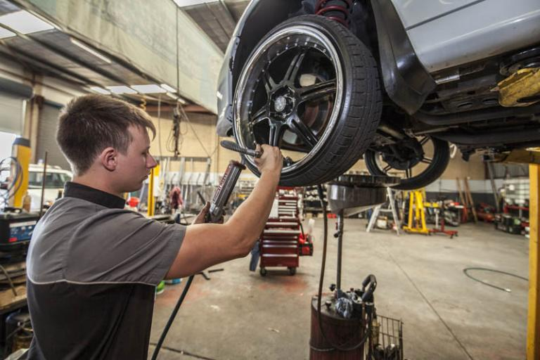 mechanic standing next to car on a lift checking the front wheel tire pressure