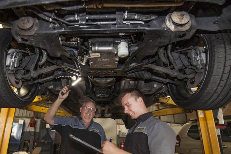 mechanics examining the underneath of a car with a torch in service centre while it is on a car lift writing down what they see