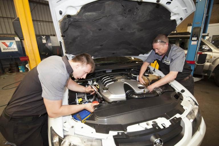mechanics examining under hood of car at the car service centre in balcatta