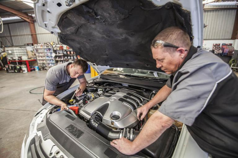 professional car mechanics looking under car hood to inspect the engine while servicing