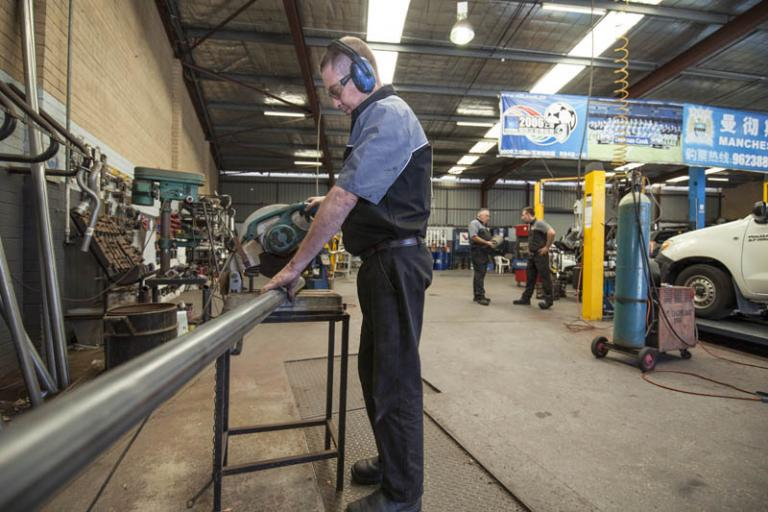 auto mechanic cuts metal with a metal grinding machine in the car servicing workshop