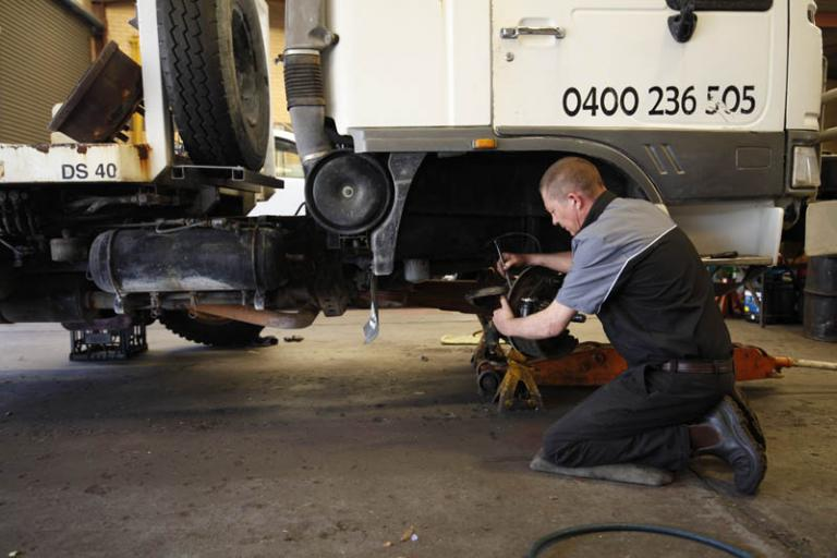 automobile mechanic repairing trucks brakes in the garage while truck is on a jack